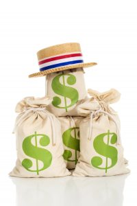 Political fund raising / contributions. A Patriotic skimmer hat sits atop a pile of money bags on a white background with a reflection